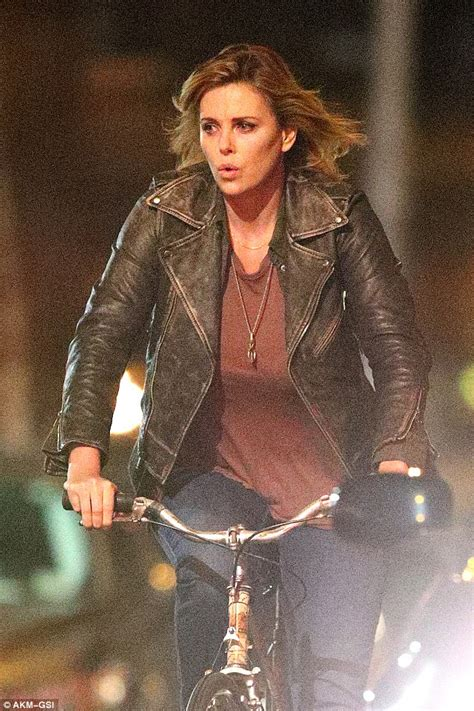 Charlize Theron shows fuller figure while riding a bike on ...