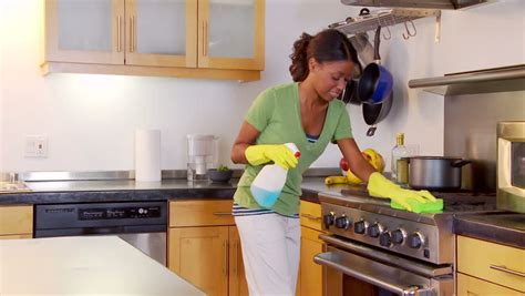 Young Woman Cleaning Kitchen Counter And Stove Stock ...